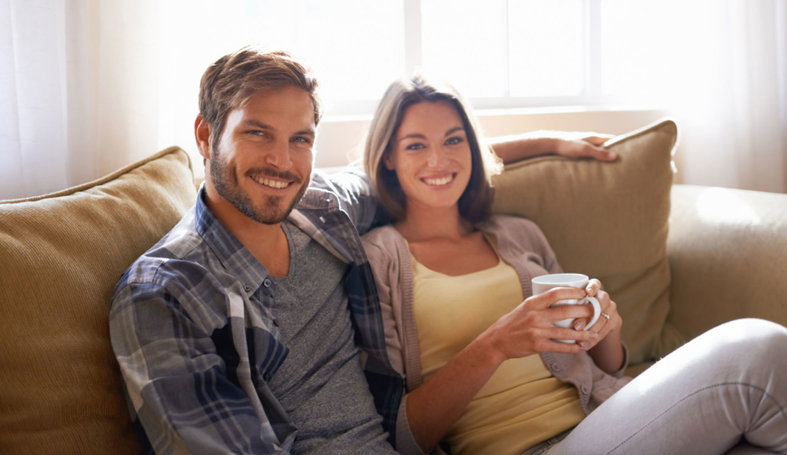 A couple sitting on a sofa and smiling