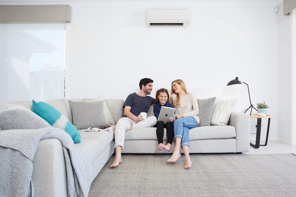 Family enjoying on a sofa under split system air conditioner